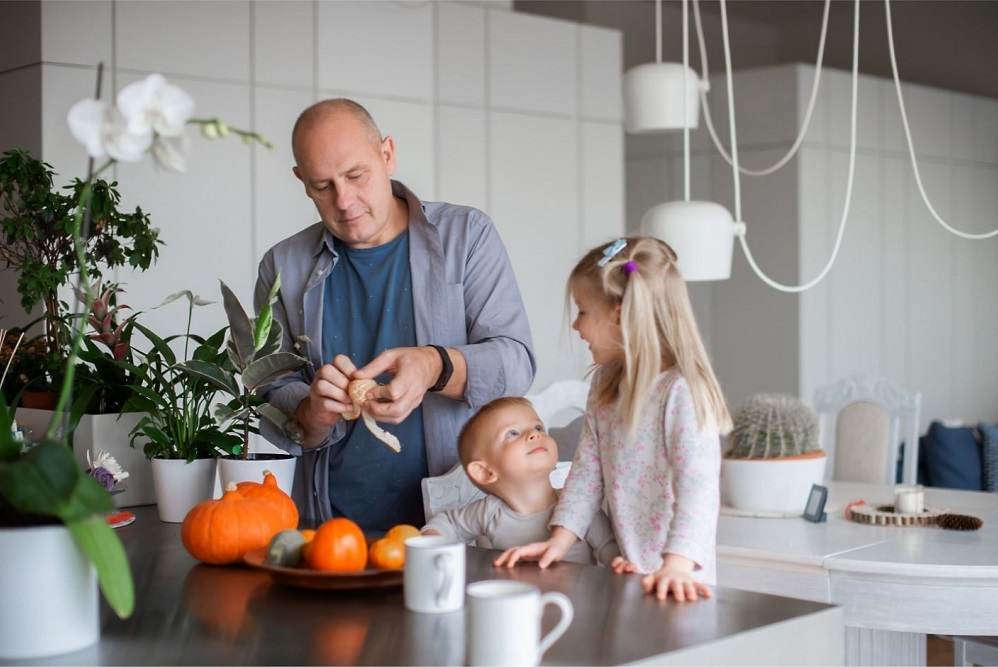 two children along with their grandfather in family kitchen